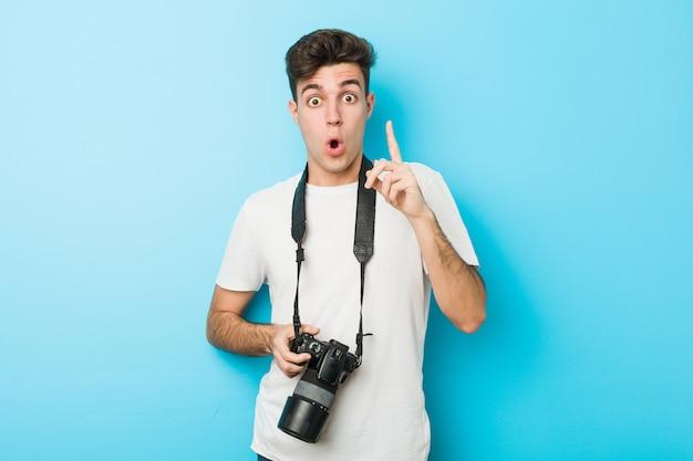 Homem jovem fotógrafo caucasiano segurando tendo uma ótima idéia, conceito de criatividade.