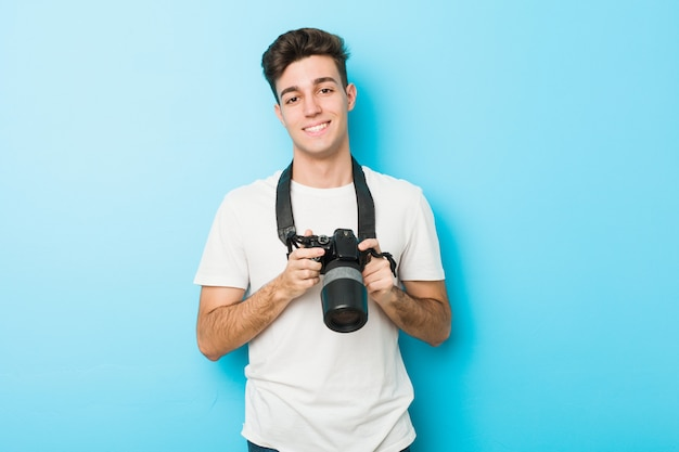 Homem jovem fotógrafo caucasiano segurando uma câmera feliz, sorridente e alegre.