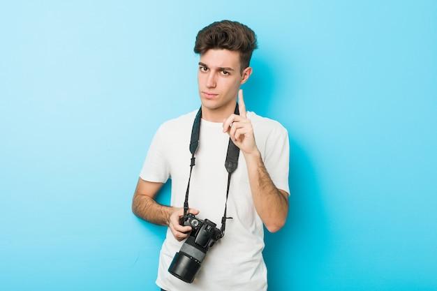 Homem jovem fotógrafo caucasiano segurando uma câmera, mostrando o número um com o dedo.