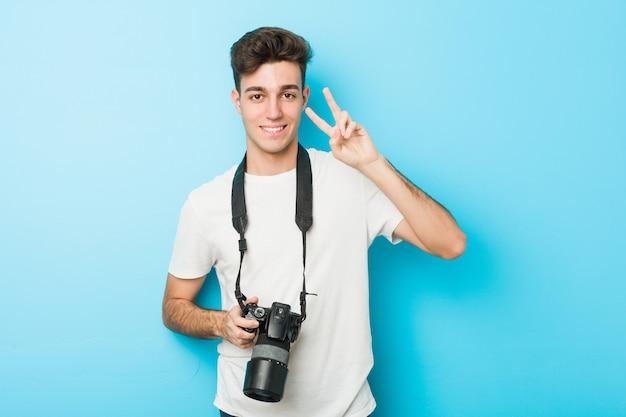 Homem jovem fotógrafo caucasiano segurando uma câmera mostrando sinal de vitória e sorrindo amplamente.