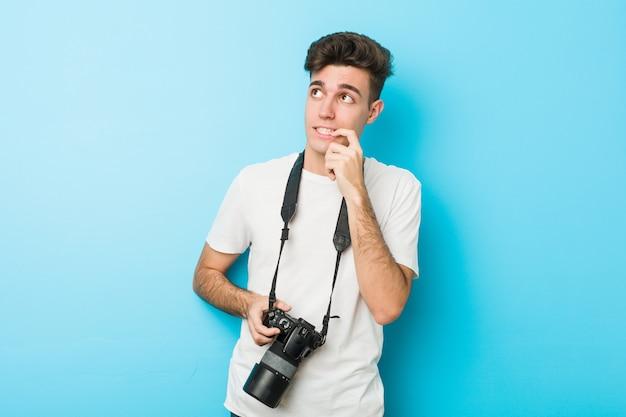 Homem jovem fotógrafo caucasiano segurando uma câmera relaxado pensando em algo