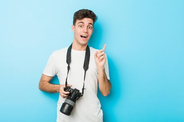 Homem jovem fotógrafo caucasiano segurando uma câmera sorrindo alegremente apontando com o dedo indicador.