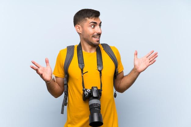 Homem jovem fotógrafo com expressão facial de surpresa