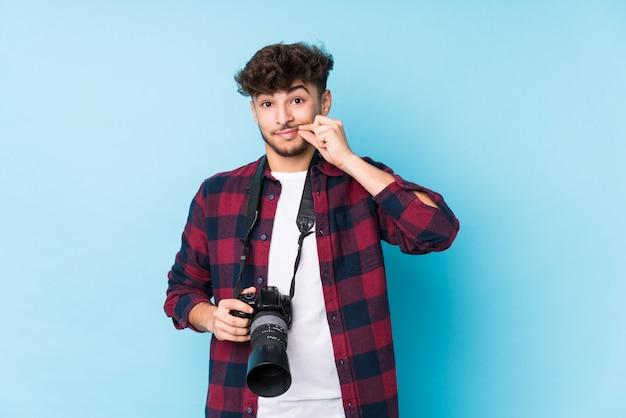 Homem jovem fotógrafo com os dedos nos lábios, mantendo um segredo.