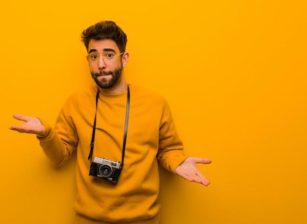 Homem jovem fotógrafo confuso e duvidoso