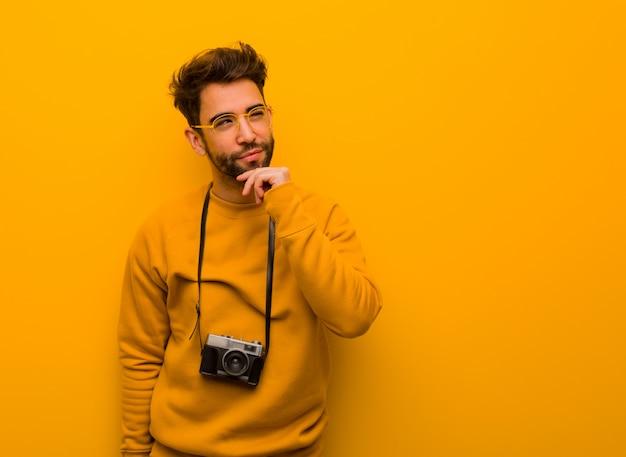Homem jovem fotógrafo duvidando e confuso