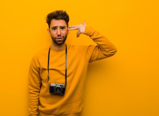 Homem jovem fotógrafo fazendo um gesto de suicídio