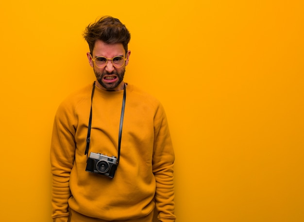 Homem jovem fotógrafo gritando muito irritado e agressivo