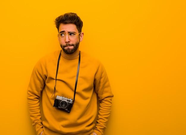 Homem jovem fotógrafo pensando em uma idéia
