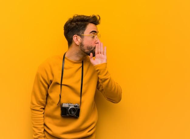 Homem jovem fotógrafo sussurrando fofoca tom