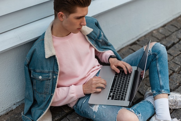 Homem jovem freelancer de sucesso em roupas jeans casuais jeans elegantes senta-se com o laptop e trabalha remotamente em um projeto criativo. designer de moda atraente está digitando no teclado. remova o trabalho.