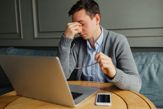 Homem jovem frustrado massageando o nariz e mantendo os olhos fechados durante o trabalho