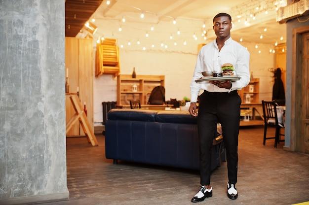 Homem jovem garçom mantém bandeja com hambúrguer no restaurante