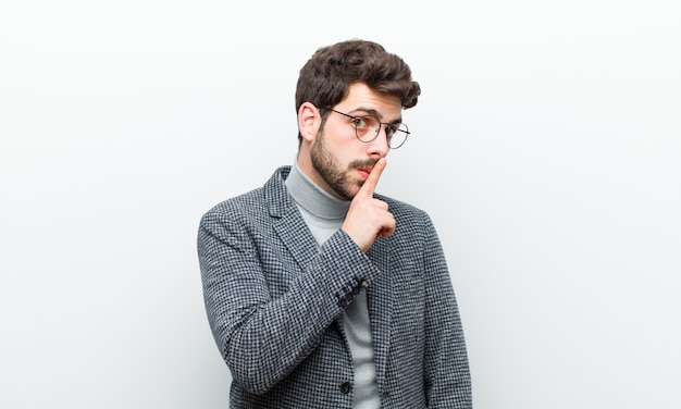 Homem jovem gerente pedindo silêncio e gesticulando quieto com o dedo na frente da boca dizendo shh ou mantendo um segredo