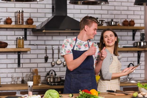 Homem jovem, gesticule, polegar, cima, para, namorada, enquanto, cozinhar, junto
