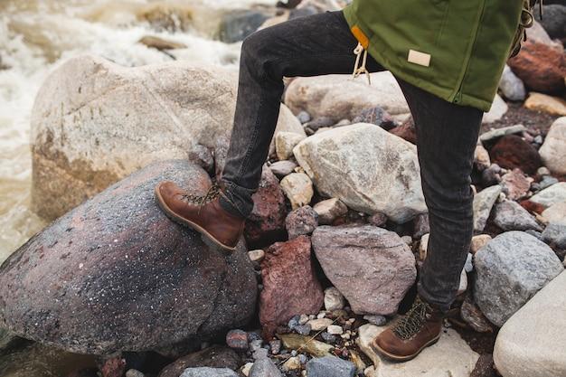 Homem jovem hippie, caminhadas na natureza selvagem, férias de inverno, viagem, sapatos quentes, botas fechadas, detalhes pés, pernas
