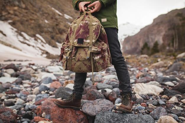 Homem jovem hippie, caminhando à beira do rio, natureza selvagem, férias de inverno, segurando uma mochila nas mãos, detalhes de close up
