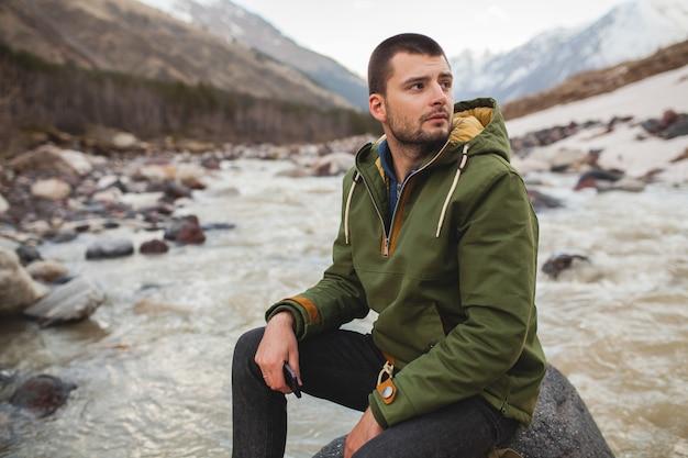 Homem jovem hippie caminhando à beira do rio, natureza selvagem, férias de inverno