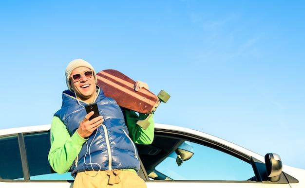 Homem jovem hippie com smartphone ouvindo música ao lado de seu carro