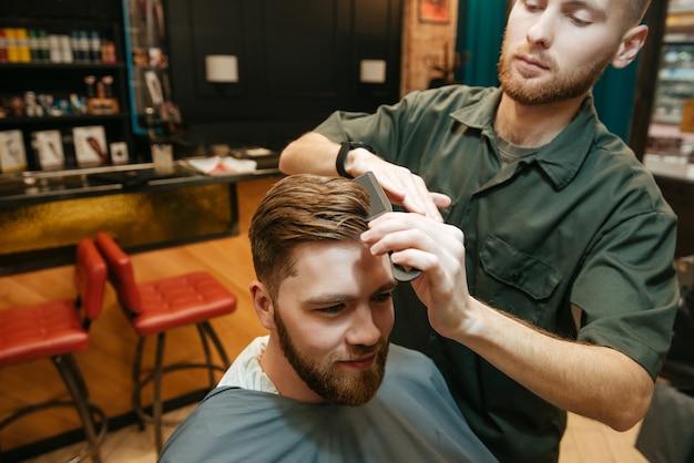 Homem jovem hippie cortando cabelo de cabeleireiro enquanto está sentado na cadeira.