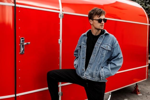 Homem jovem hippie elegante com uma jaqueta jeans azul da moda