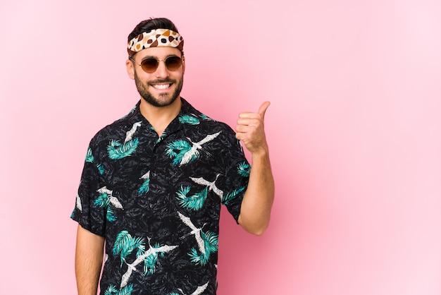 Homem jovem hippie isolado sorrindo e levantando o polegar