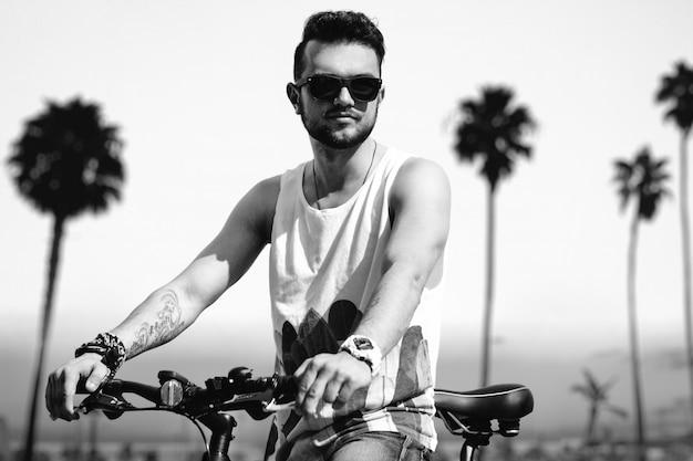 Homem jovem hippie na praia em dia ensolarado de verão com bicicleta