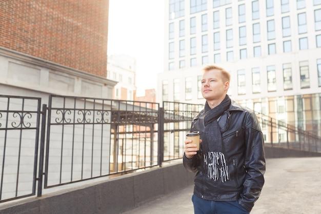 Homem jovem hippie na rua tomando café em um dia ensolarado