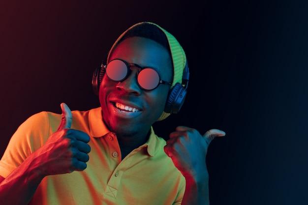 Homem jovem hippie ouvindo música com fones de ouvido no estúdio preto com luzes de néon.
