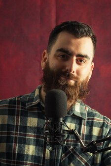 Homem jovem hippie perto de um microfone de streaming sorrindo