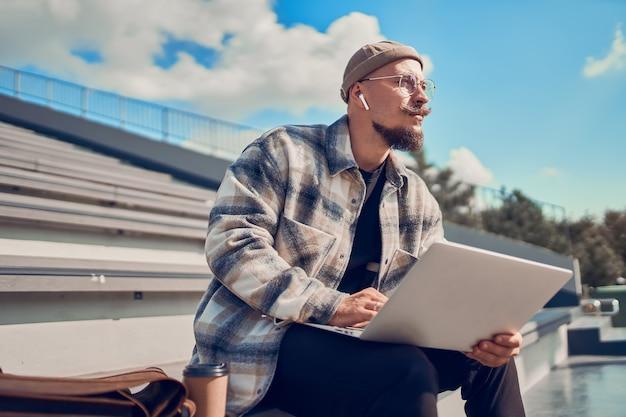 Homem jovem hippie sentado ao ar livre com café enquanto trabalha no blog, estudando olhares à sua frente