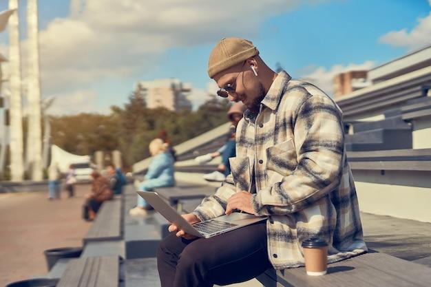 Homem jovem hippie sentado ao ar livre tomando café enquanto verifica o e-mail, trabalhando em um blog e estudando on-line
