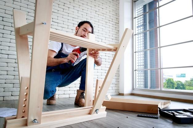 Homem jovem hippie trabalhando como faz-tudo, montando mesa de madeira com equipamentos, conceito para bricolage em casa e self-service. no escritório.