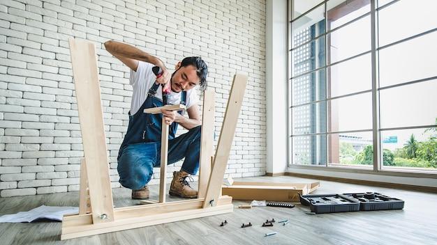 Homem jovem hippie trabalhando como faz-tudo, montando mesa de madeira com equipamentos, conceito para casa diy e self-service. no escritório há uma parede de bloco de tijolo branco.