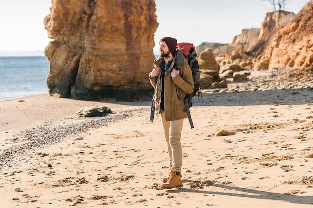 Homem jovem hippie viajando com mochila na costa do mar de outono, vestindo jaqueta e chapéu.