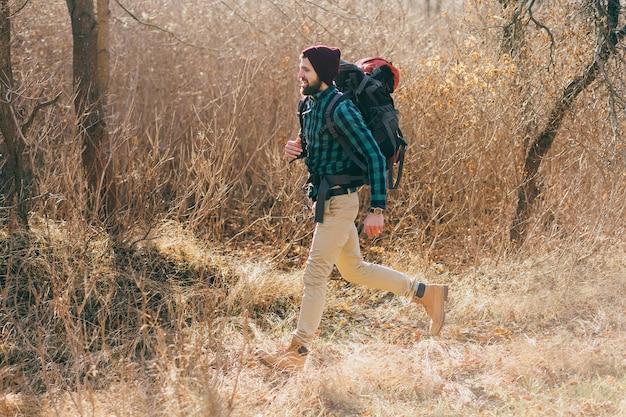 Homem jovem hippie viajando com mochila na floresta de outono, usando camisa xadrez e chapéu.