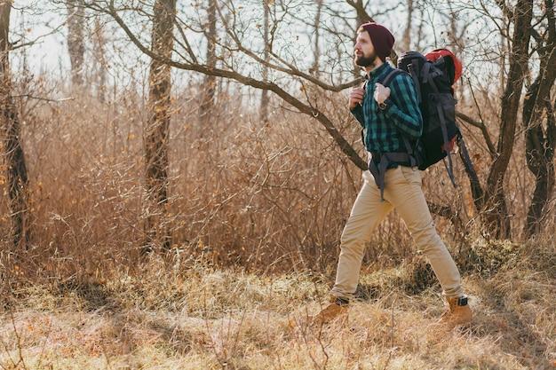 Homem jovem hippie viajando com mochila na floresta de outono, usando chapéu e camisa quadriculada, turista ativa caminhando, explorando a natureza na estação fria