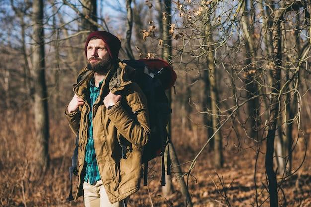 Homem jovem hippie viajando com mochila na floresta de outono, vestindo jaqueta e chapéu, turista ativo, explorando a natureza na estação fria