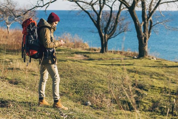 Homem jovem hippie viajando com mochila, vestindo jaqueta e chapéu, turista ativo, usando telefone celular, explorando a natureza na estação fria