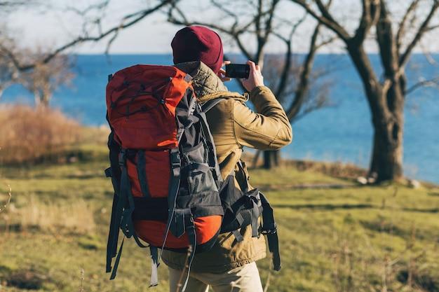 Homem jovem hippie viajando com uma mochila de casaco quente e chapéu, turista ativo, tirando fotos no celular, explorando a natureza na estação fria