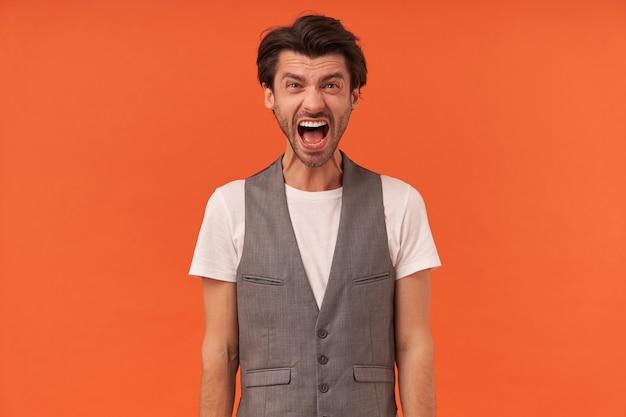 Homem jovem histérico irritado com barba por fazer e boca aberta olhando para a câmera e gritando