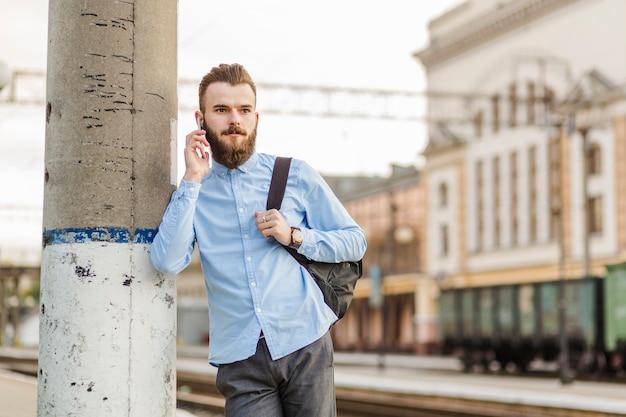 Homem jovem, inclinar-se, coluna, falando, ligado, cellphone, em, estação de comboios