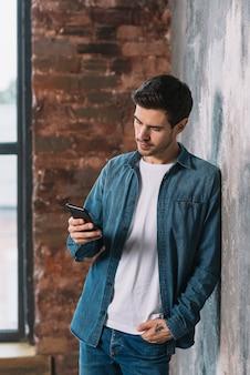 Homem jovem, inclinar-se, frente, parede, usando, telefone pilha