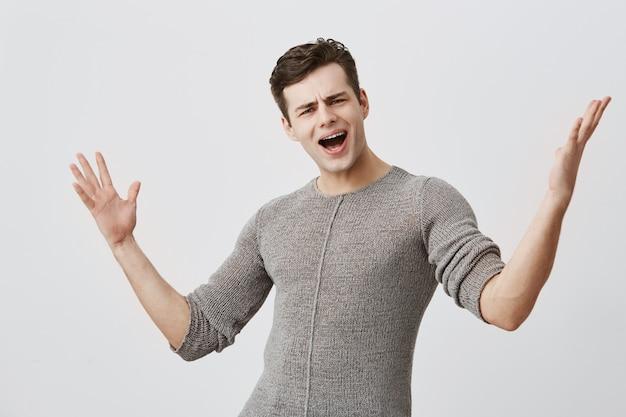 Homem jovem insatisfeito com cabelos escuros fecha os olhos e grita alto, gestos, sendo muito emocional após a aprovação no exame, isolado. homem emocional atraente na camisola