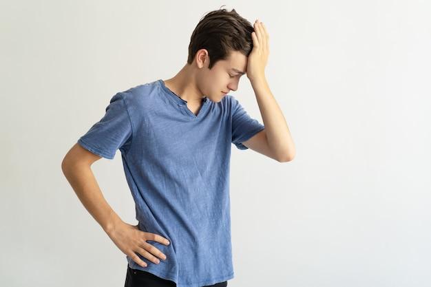 Homem jovem intrigado, segurando a testa enquanto se sente stress
