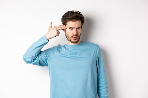Homem jovem irritado com a testa franzida, mostrando o gesto de atirar perto da cabeça, sinal de estourar o cérebro, de pé sobre um fundo branco