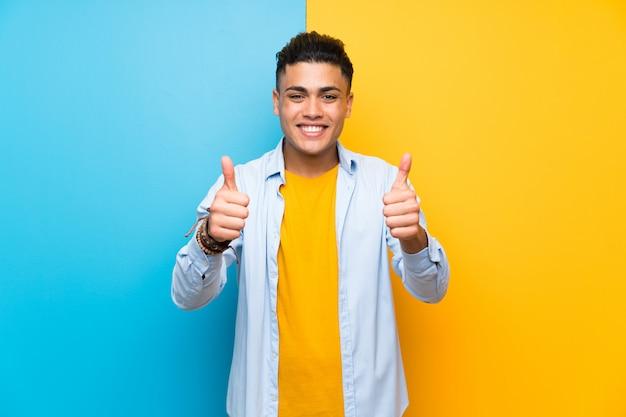 Homem jovem, isolado, colorido, dar, um, polegares cima, gesto