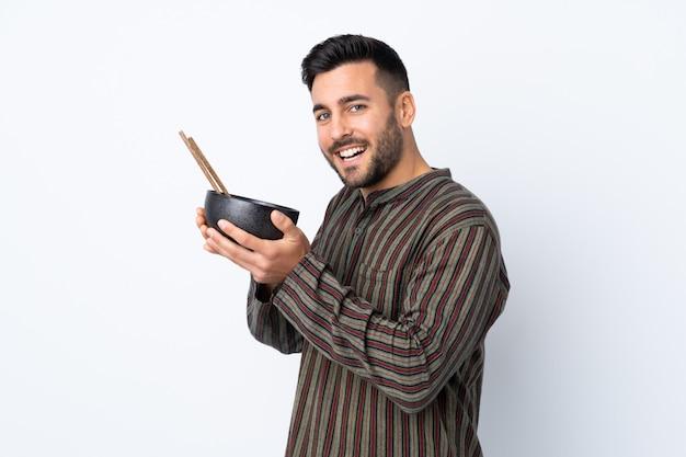 Homem jovem, isolado, parede, segurando, um, tigela macarrão, com, pauzinhos