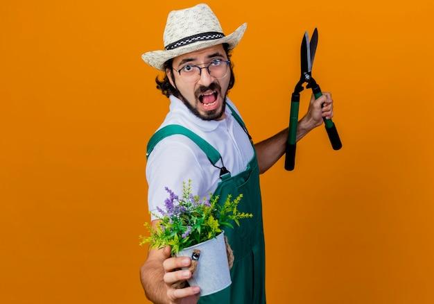 Homem jovem jardineiro barbudo usando macacão e chapéu segurando uma tesoura de cerca-viva mostrando um vaso de planta gritando e ficando desapontado em pé sobre um muro laranja