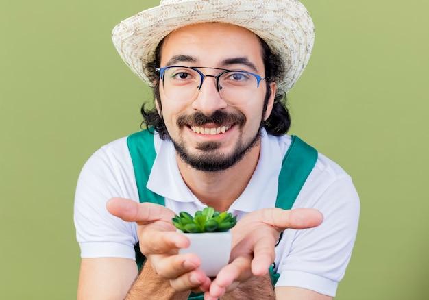 Homem jovem jardineiro barbudo vestindo macacão e chapéu mostrando uma planta em um vaso olhando para a frente sorrindo alegremente em pé sobre a parede verde-clara